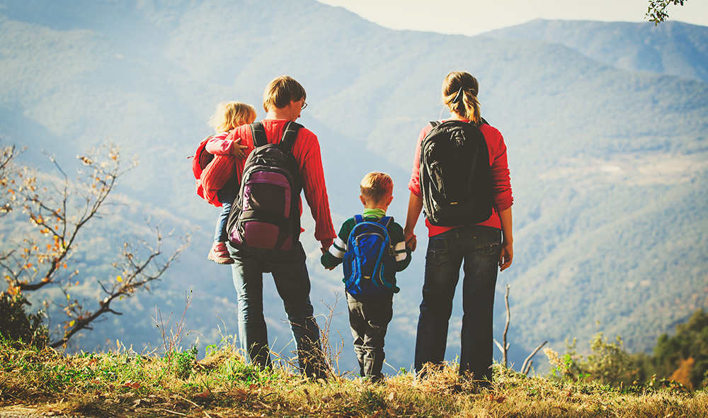 משפחה של אבא, אמא, ילד וילדה מטיילים בחיק הטבע ומחזיקים ידיים