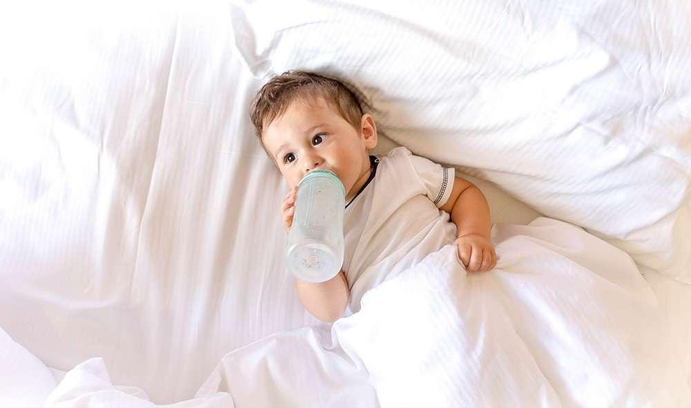 תינוק שותה מים מבקבוק במיטה