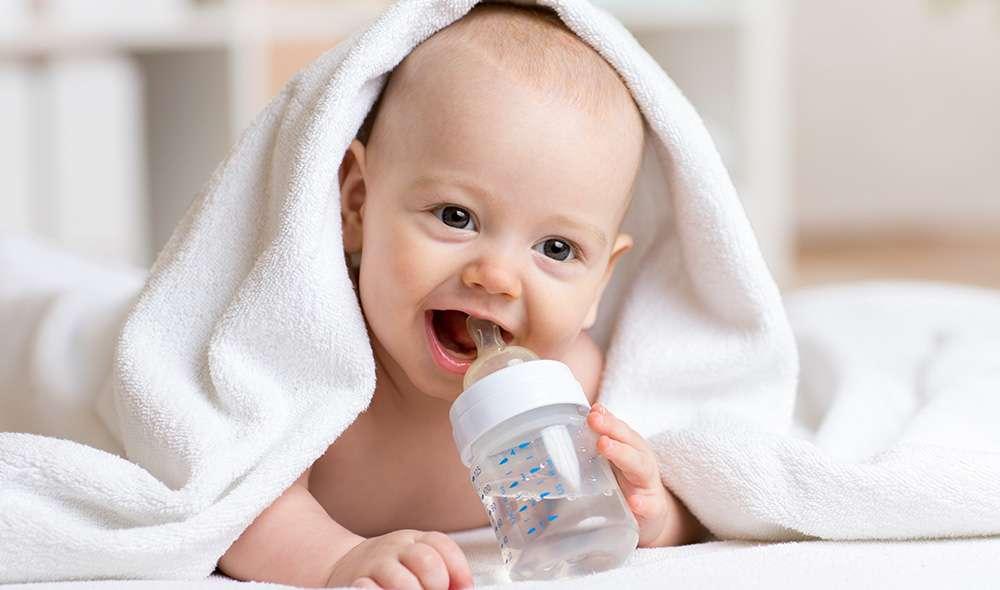 תינוק חייכן שוכב מתחת למגבת ומחזיק בקבוק מים בפיו