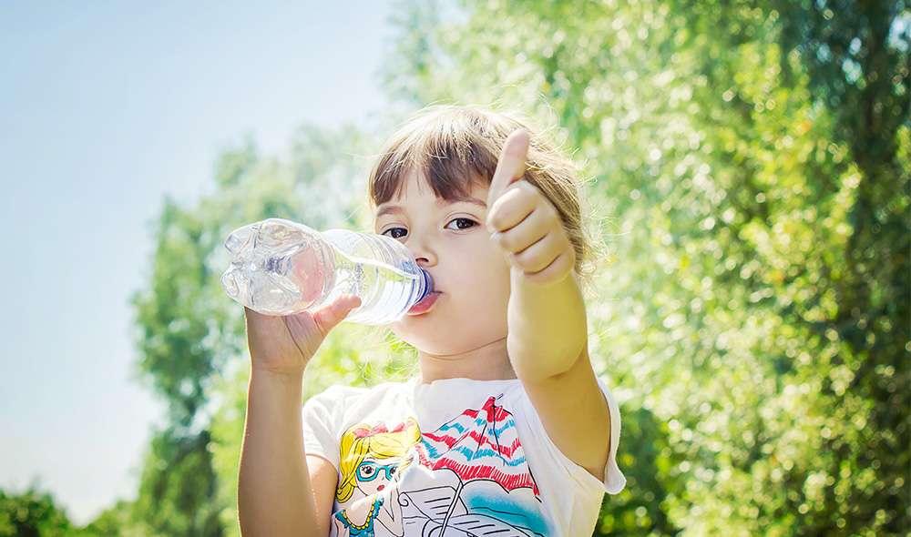 ילדה שותה מים מבקבוק בחוץ ומסמנת לייק עם האגודל