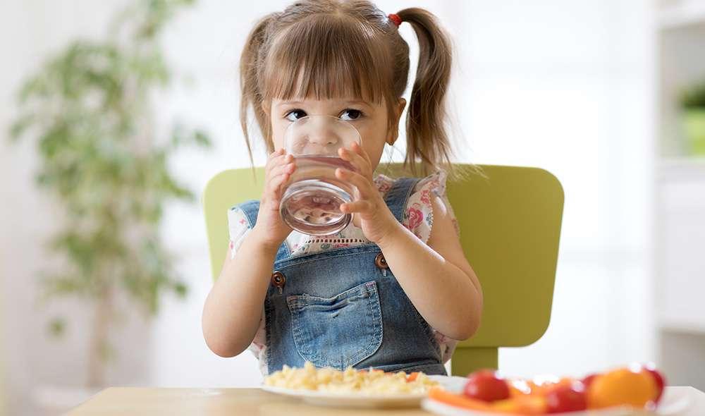 ילדה עם קוקיות יושבת ליד שולחן ושותה מים מכוס