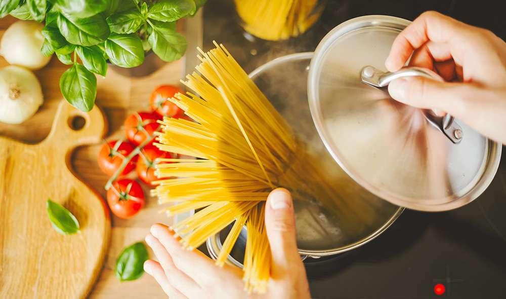 סיר עם ספגטי ומים ממבט על, לצידו עגבניות ובזיליקום