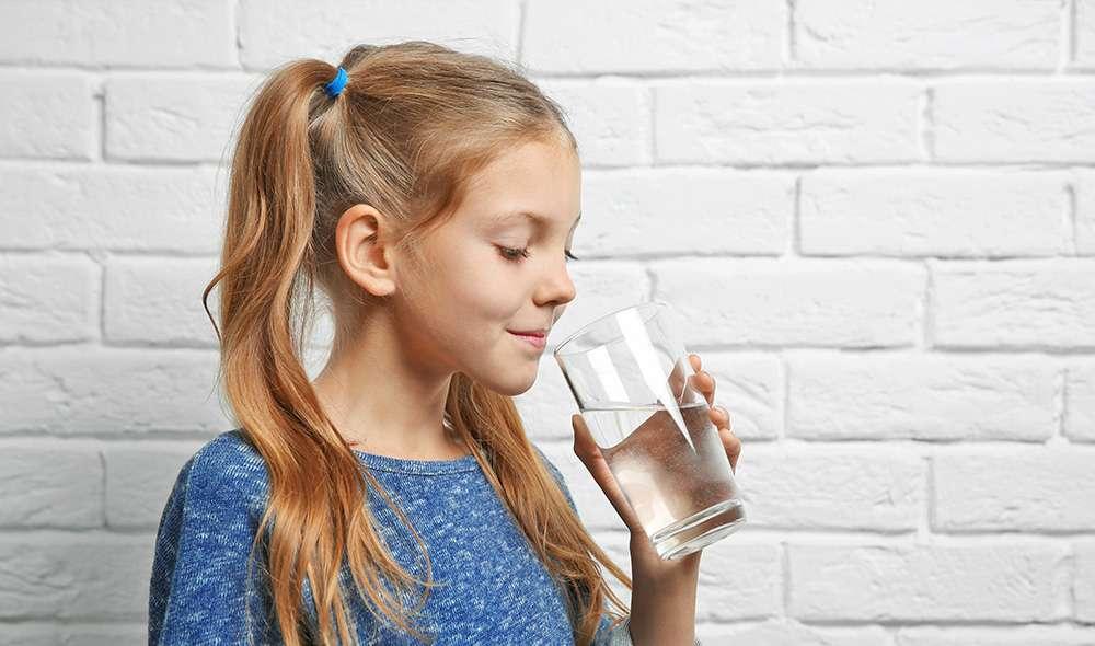 ילדה עם קוקיות עומדת ליד קיר ומביטה לתוך כוס מים