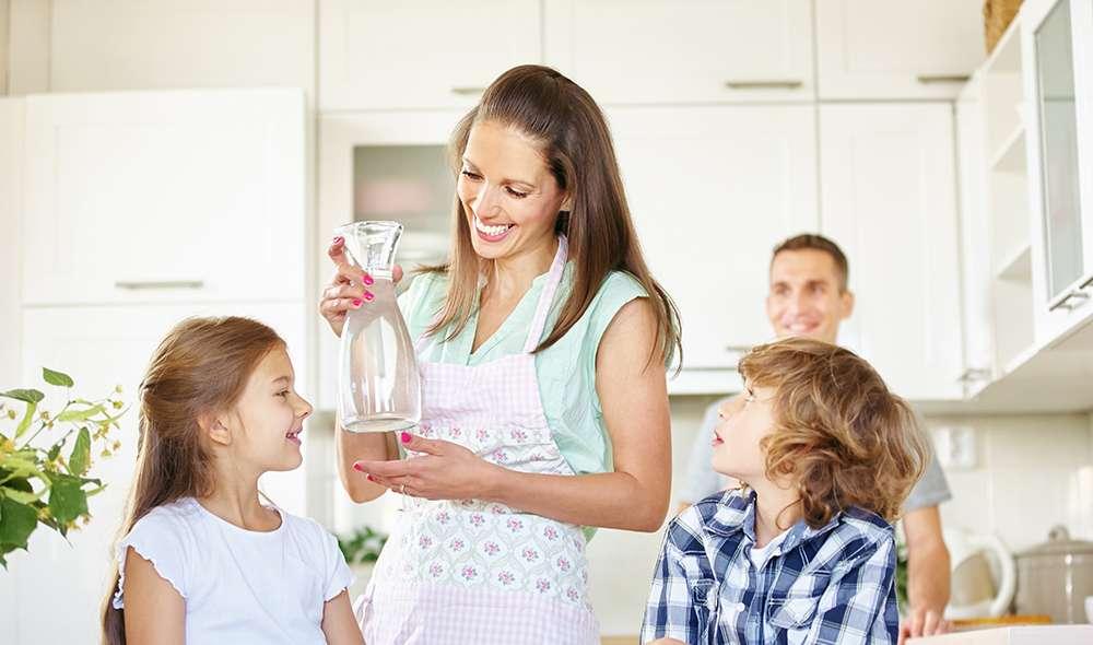 אמא מחזיקה קנקן מים ביד, יחד עם שני ילדיה ובעלה במטבח