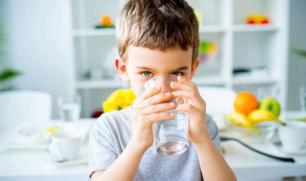 ילד יושב במטבח ושותה מים מכוס