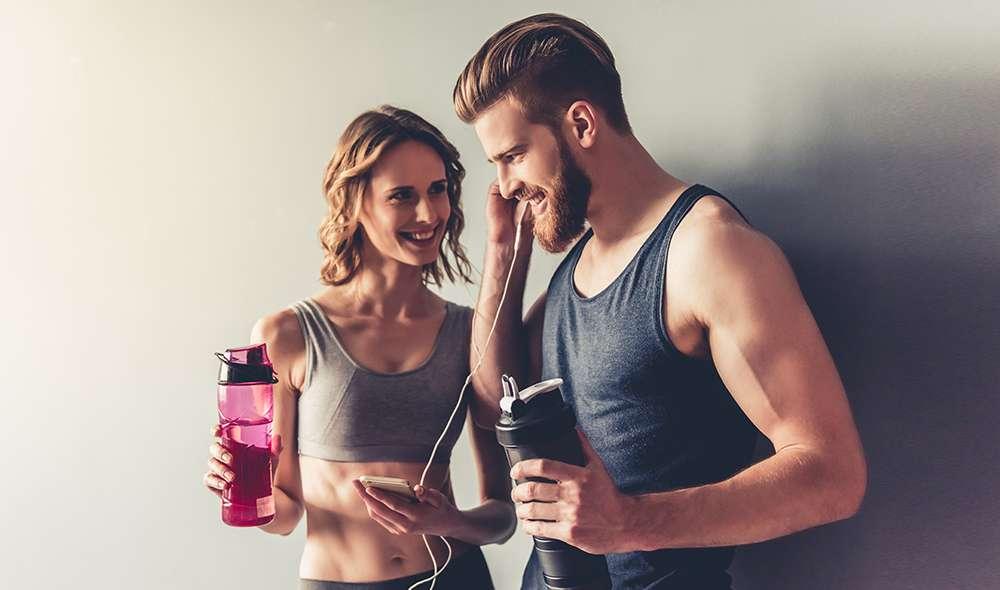 זוג אחרי אימון מחזיק בקבוקי מים ביד, ומאזין במשותף לאוזניות