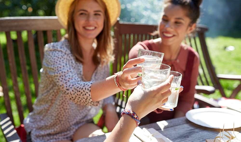 שלוש בחורות משיקות כוסות מים לחיים בחיק הטבע