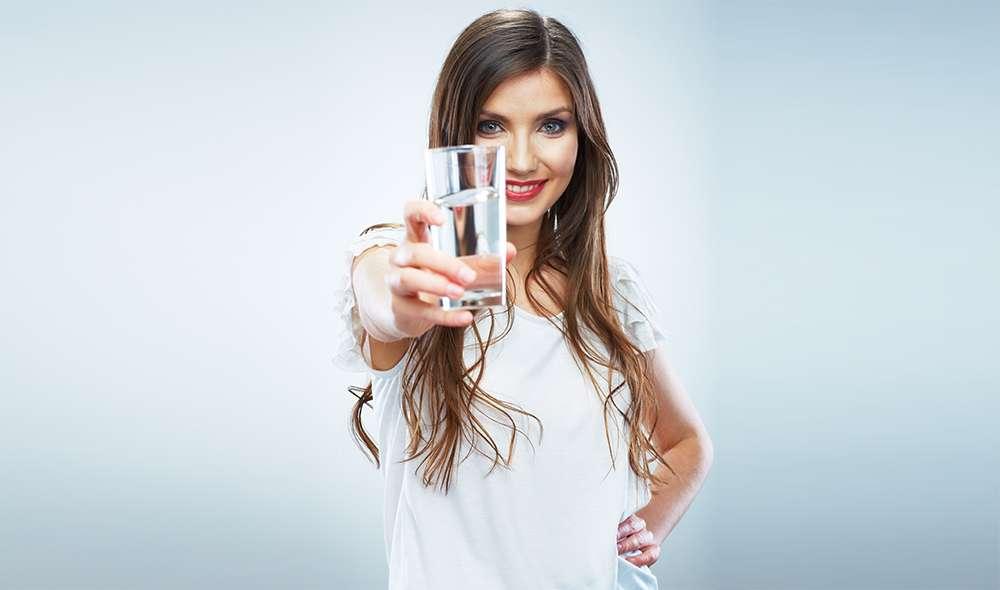 אישה מושיטה יד עם כוס מים קדימה