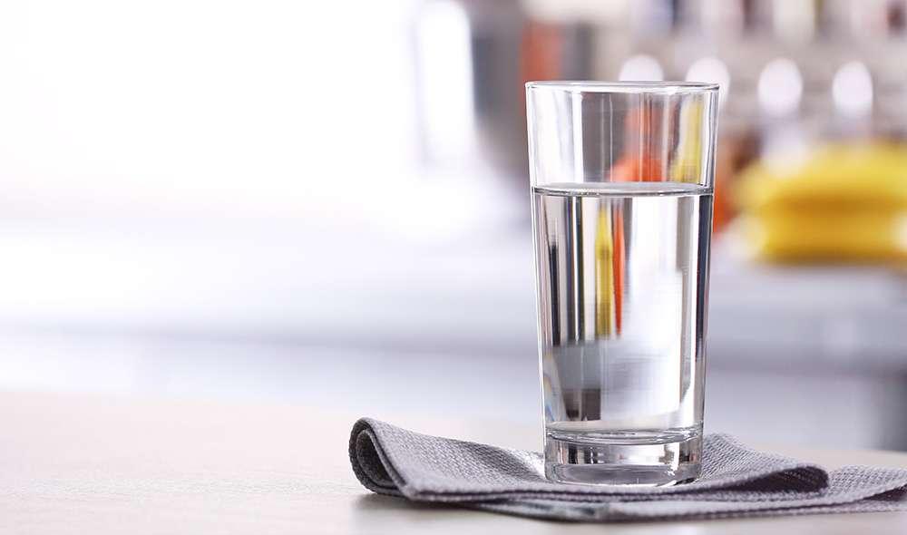 כוס מים מונחת על מפית שנמצאת על השיש