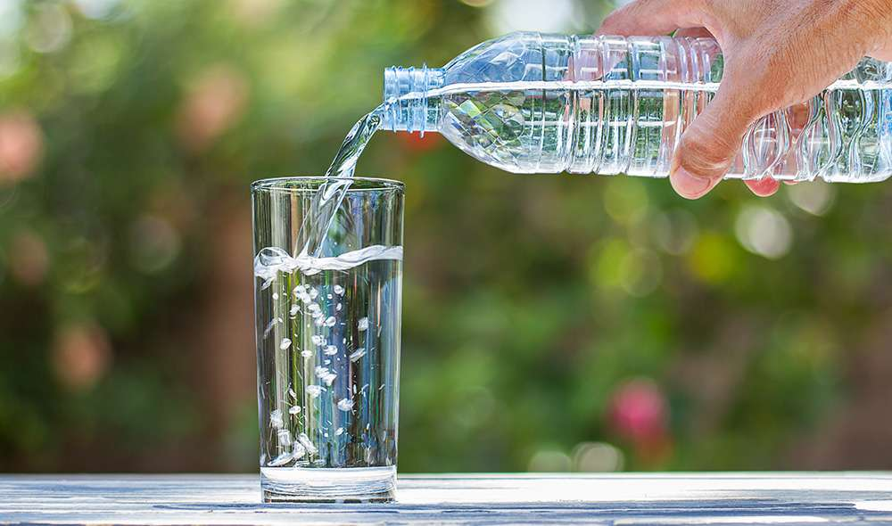 יד מוזגת מים מבקבוק לכוס
