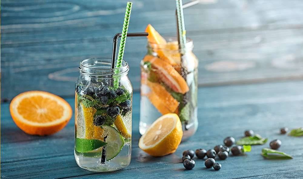 שתי צנצנות מלאות במים, פירות הדר, אוכמניות וקשים לשתיה