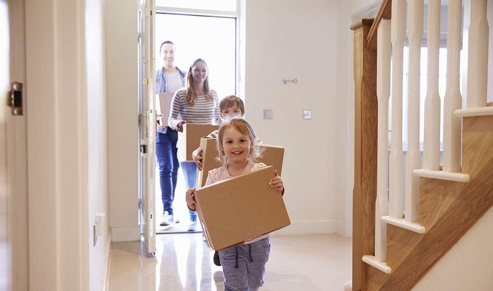 משפחה נכנסת לבית חדש עם ארגזים בידיים