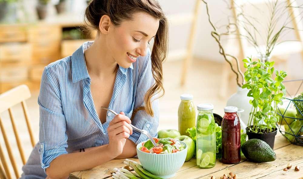 בחורה יושבת ליד שולחן ואוכלת סלט ירקות, ליד הקערה מונחים רטבים שונים