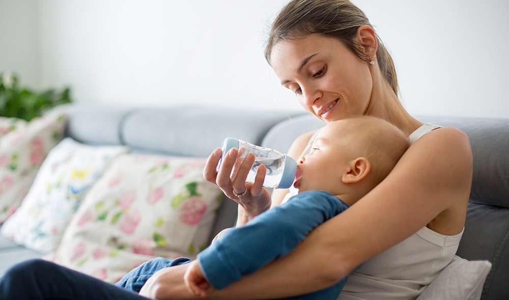 אם צעירה יושבת על ספה ונותנת לבנה התינוק לשתות מים מבקבוק