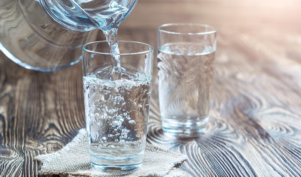מים נמזגים לכוס מקנקן, לידה כוס אחרת מלאה במים