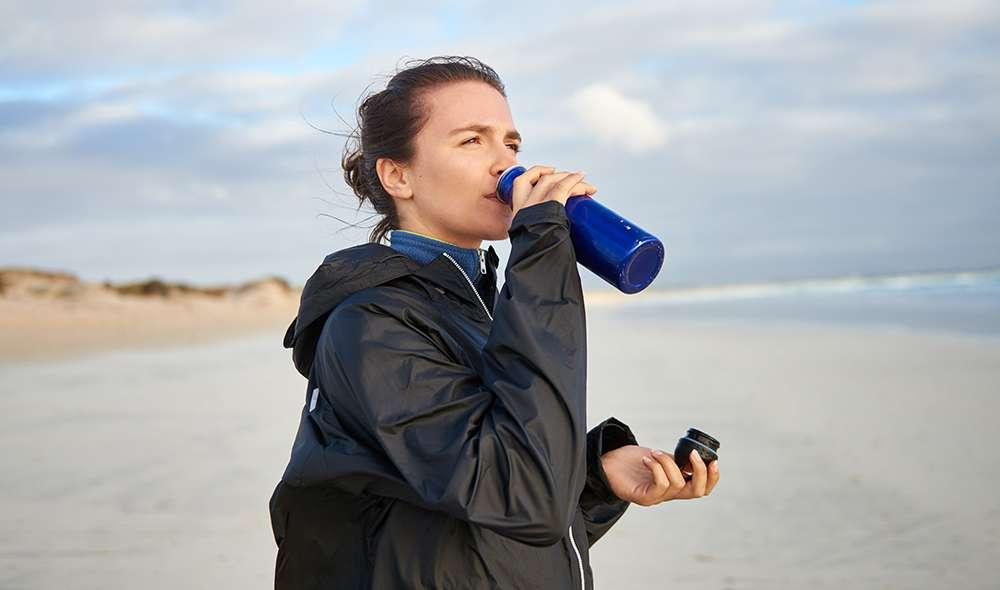 אישה שותה מים מבקבוק בחוף הים