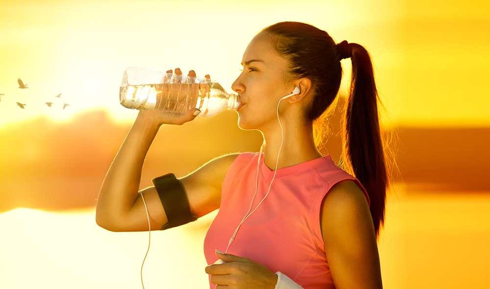 אישה בזמן אימון בחוץ שומעת מוזיקה באוזניות ושותה מים מבקבוק