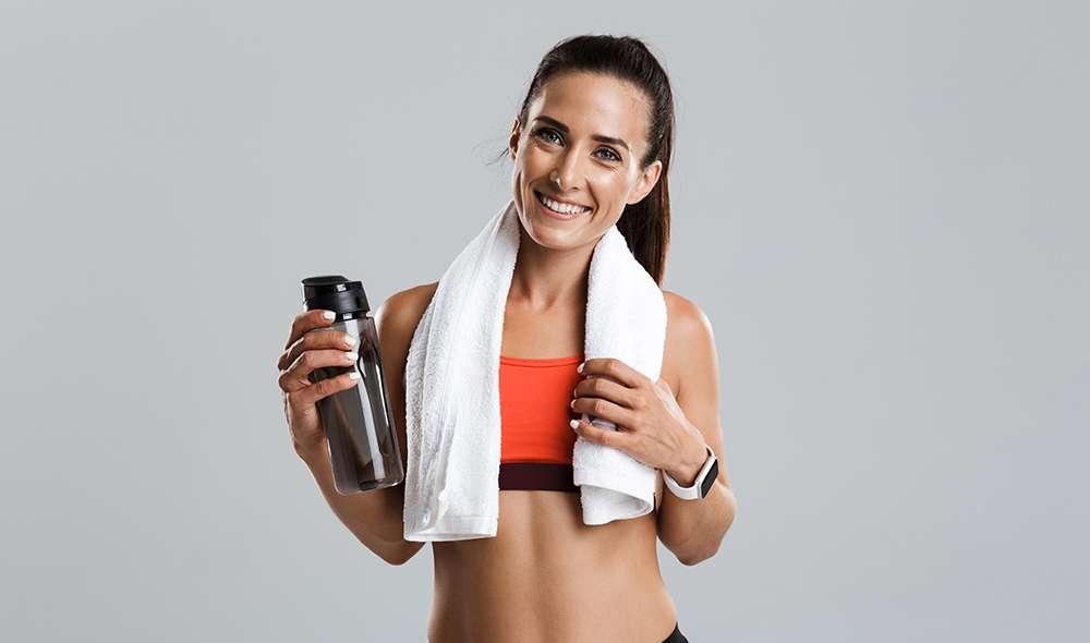 אישה אחרי אימון עם מגבת על הצוואר ובקבוק מים ביד
