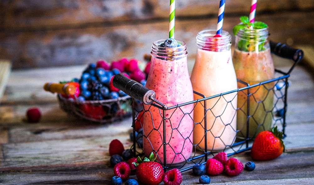 שלושה בקבוקים מלאים בשייקים של פירות בצבעים שונים, מסביבם מפוזרים פירות יער