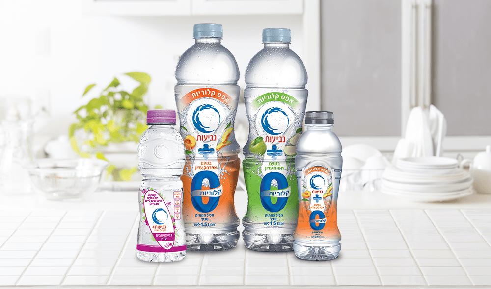 ארבעה בקבוקי מים של נביעות בגדלים שונים על שולחן מטבח